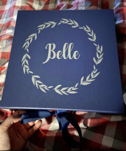 A dark blue rectangular gift box with leafs and the name Belle in the middle in silver