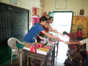 Handing out dental products and school supplies in India