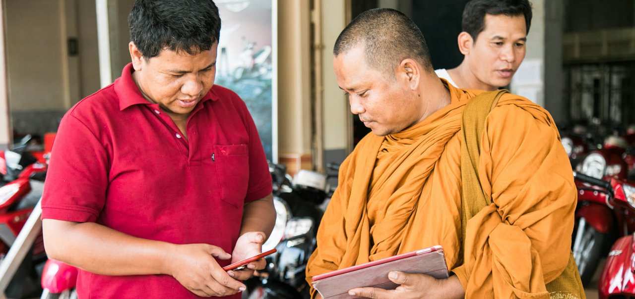 Buddhist monk choosing a motorbike in Cambodia