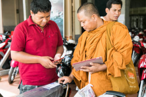 Buddhist monk picks out the perfect motorbike in Cambodia
