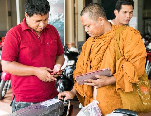 Buddhist monk choosing a motorbike in Cambodia