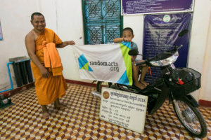 One of the monks and a local child pose with the new motorbike
