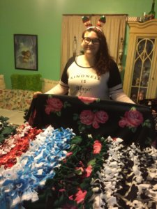Dreana posing with the twelve blankets made for Mercy House residents.