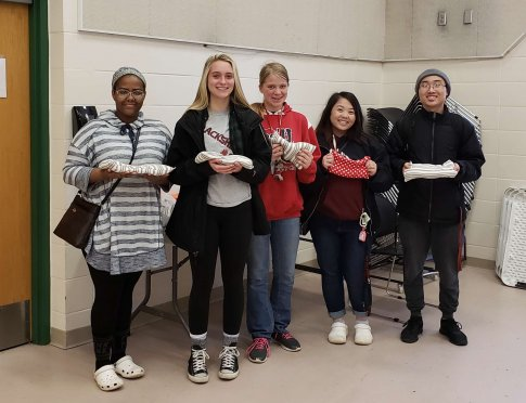 group of students posing with playthings they crafted for shelter pets