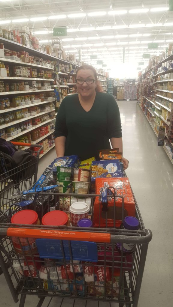 Heather in a grocery store, with supplies for homeless youth.