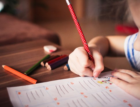 Image of a child sitting at a table and writing with colored pencils.