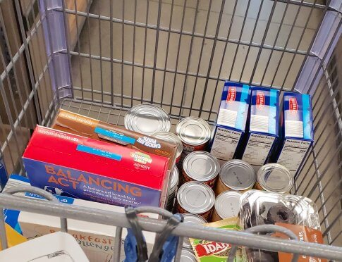 Image of grocery cart full of boxed, canned and dry goods.