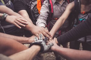A group of people standing with their hands on top of each others in a circle