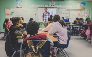 Photo of students sitting at desks in a classroom with a teach standing in front of a whiteboard.