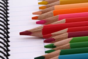 Photo of colored pencils in yellows, oranges, reds, greens and blues laying on top of blank lined notebook apper.