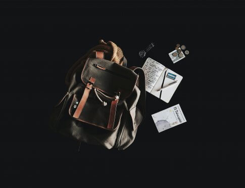 Photo of a grey backpack with notebooks, pencils and other school supplies lying next to it over a black background.