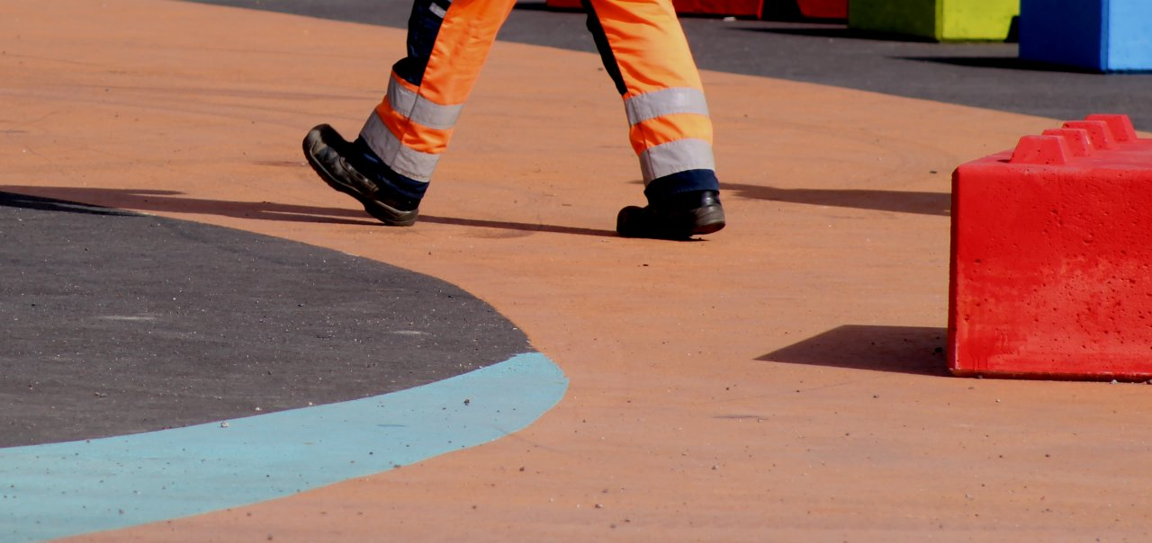 A peron walks through a concrete plaza wearing orange safety pants and black boots. In the background are red, green and blue life-sized building blocks.