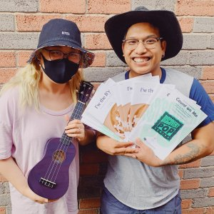 Two people hold a purple ukulele and an assortment of sheet music