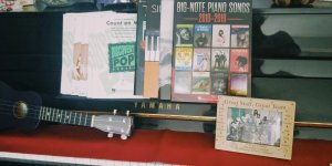 A purple ukulele and an assortent of sheet music displayed on a piano