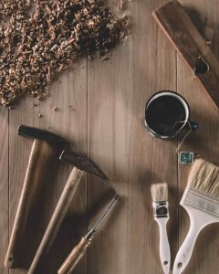 Woodworking tools are laid out on a light brown, wooden table.  Rotating clockwise, the tools include woodshavings, a ruler and a can of stain, paint brushes and hammers.