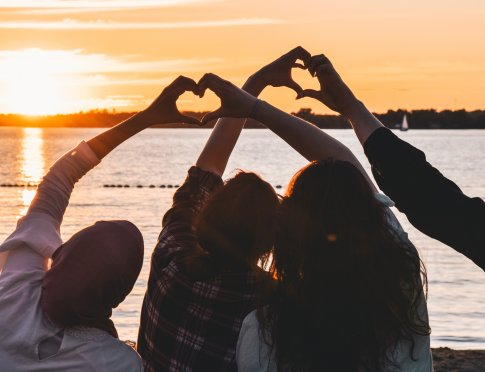 People at sunset making hearts with their hands