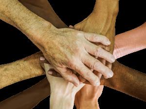 Several hands piled/joined together to symbolize teamwork
