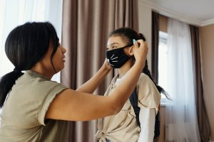 a mother placing a mask on her child's face