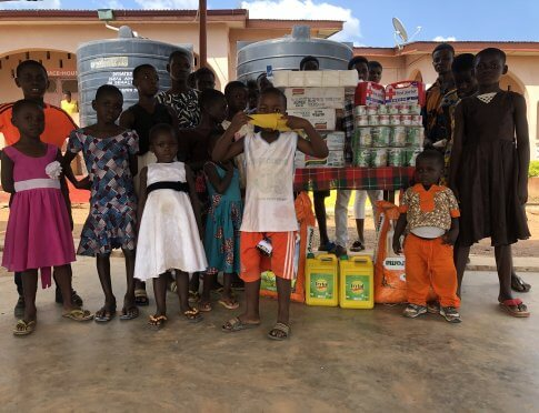 Children standing with donations