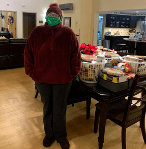 Image of Dreana wearing a red hat with a fuzzy topknot, a red jacket, and a green/teal mask standing next to the dark wood table laden with gift baskets and assorted food items.