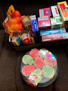 Image of a platter of Christmas cookies with red and green sprinkles, a bag of oranges, and an assortment of boxed food goods.