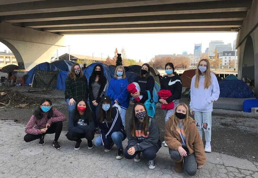 A group of masked teenagers standing in front of many tents