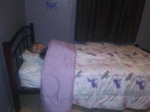 Small child under a purple unicorn blanket on a small bed.