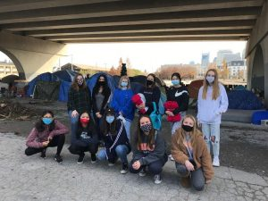 A group of young people in masks stand together in front of tents