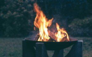 a photograph of a black iron fire bowl with a lit fire inside.