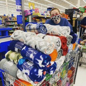 A woman in a mask behind a shopping cart full of blankets
