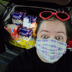 A woman in a mask stands in front of a car trunk full of food