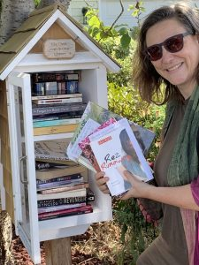 Woman puts books in a Free Little Library