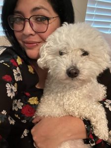 Paulina Fangel and her dog take a selfie. She's wearing a black sweater with red, yellow, and white flowers depicted. She has on dark, thin rimmed glasses.