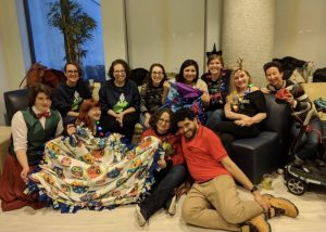 11 people sitting on a couch and the floor smile for a photo with some blankets and crafts they made