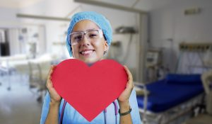 A female nurse in blue scrubs holding a red cartoon heart