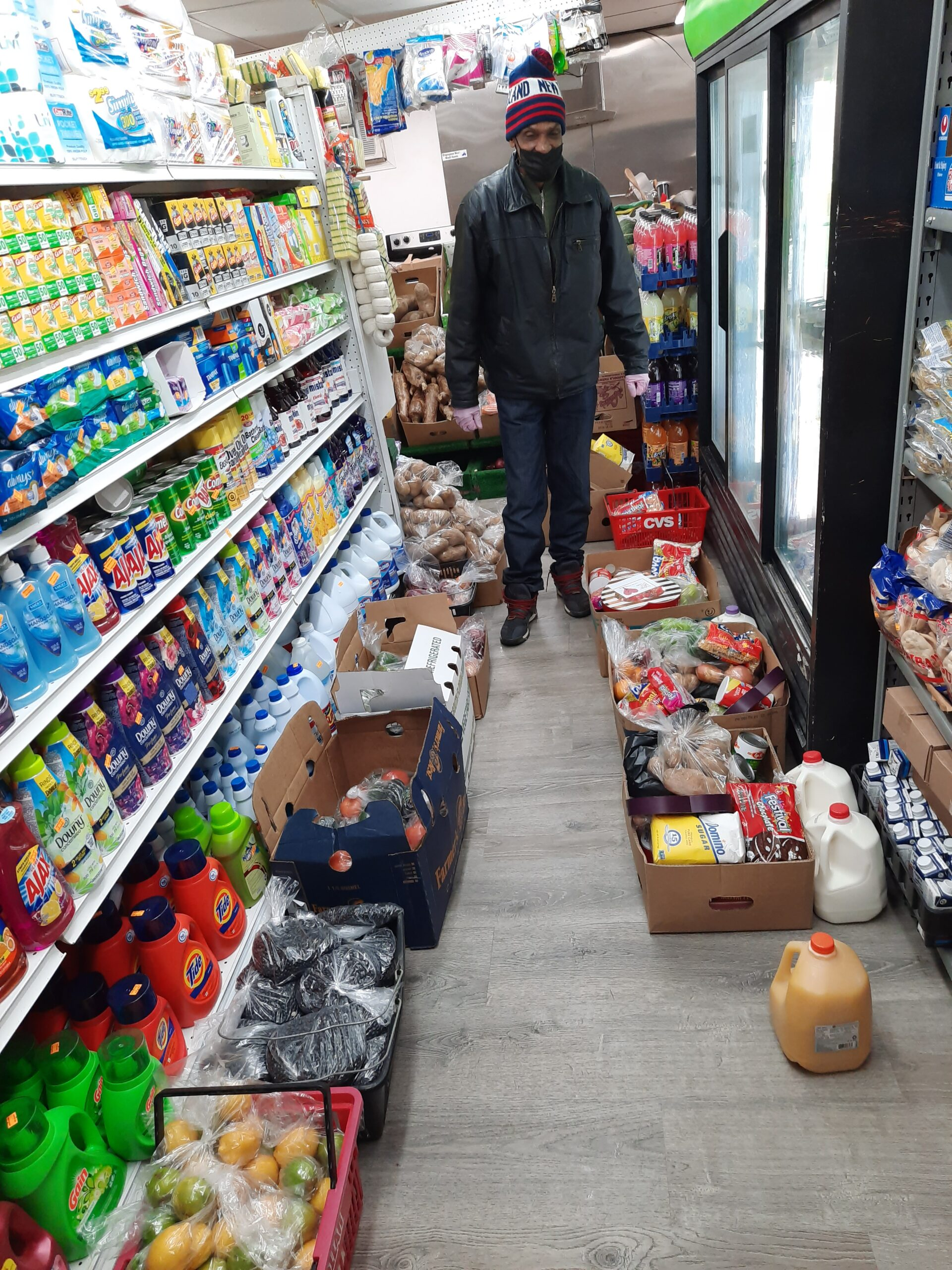 Image of a man wearing a black beanie, black jacket, and jeans standing at the far end of a grocery store facing the camera. To the left are shelves of bottles and to the right are freezers. In the floor, groceries are piled up to be packed into a car and sent to food insecure families in Lawrence, MA.