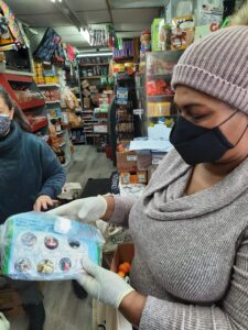 Image of a woman wearing a beige beanie with a puffy beige ball on top; a black mask; and a beige, long-sleeve sweater. She is wearing gloves as she handles a clear, plastic bag which appears to hold a plastic bottle of face wash with an advertisement written in another language - most likely Spanish.