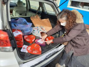 Image of a woman wearing a brown winter jacket and a mask leaning over the trunk of a silver unidentified SUV taping printed cards with hearts on white paper onto red, heart-shaped boxes of chocolates..