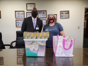 Misty and Gadsden County School District's superintendent pose with her gift of 155 boxes of Colors of the World crayons