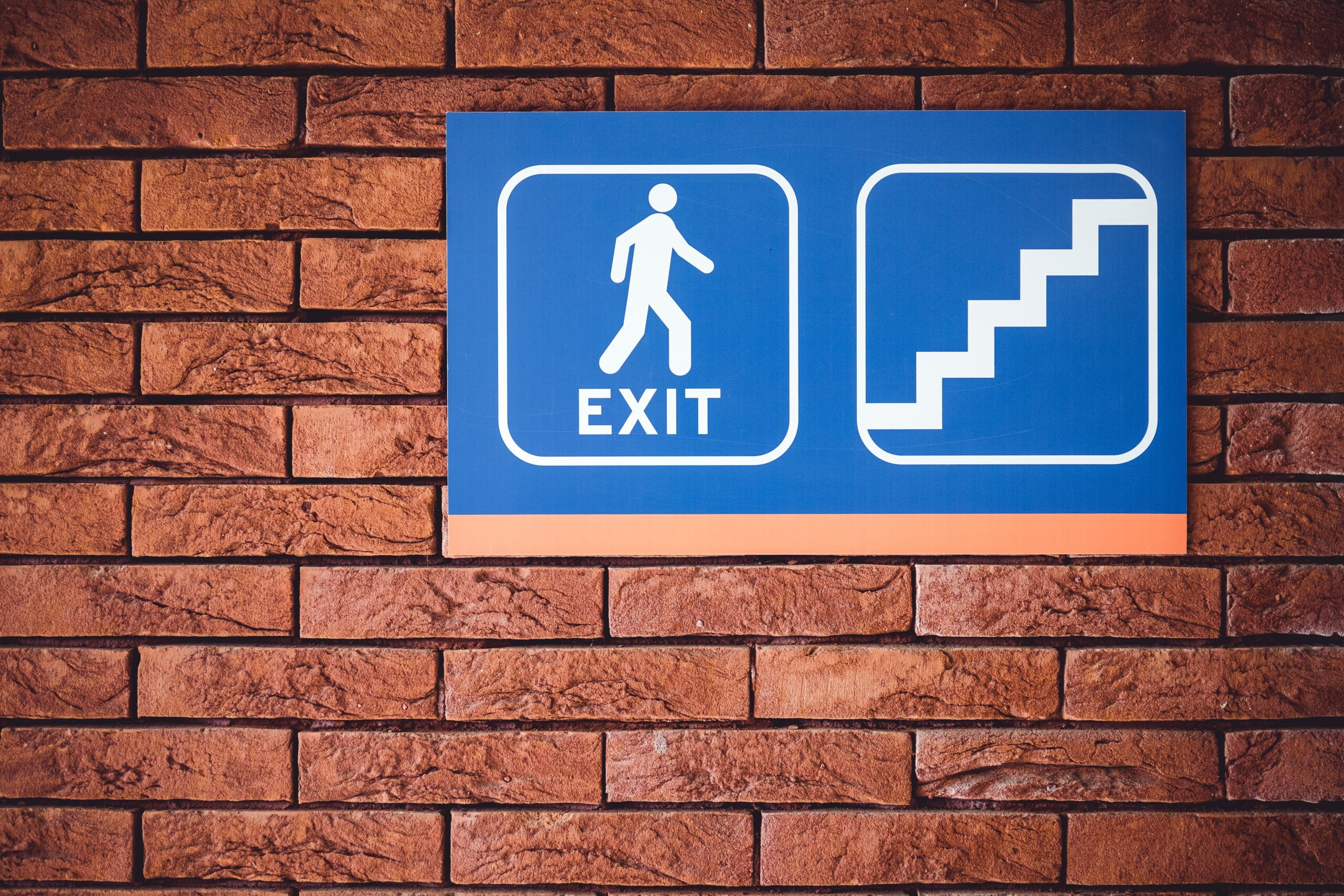 """Red brick wall with a blue plastic sign hanging on it. Two pictures inside round-cornered boxes in white lines. One shows a human figure walking and reads """"EXIT"""". The other box shows a staircase."""