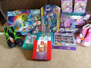 Image of unwrapped presents including boots, toys, dolls, and action figures sitting on a beige carpet.