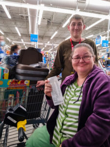 two people, one standing one seated, show a receipt after purchasing kitcehn and home supplies