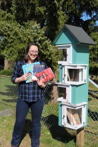 A woman is standing with books in her hands in front of a Little Free Library, ready to donate some diverse children's books