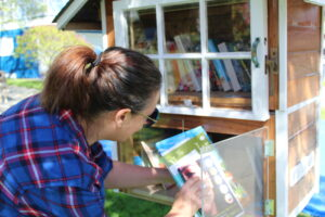 A woman puts some books into a little free library