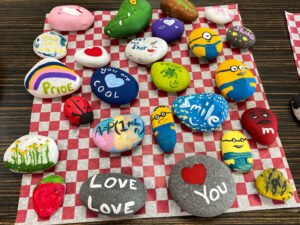 Smooth rocks painted with pictures, cartoons, and messages