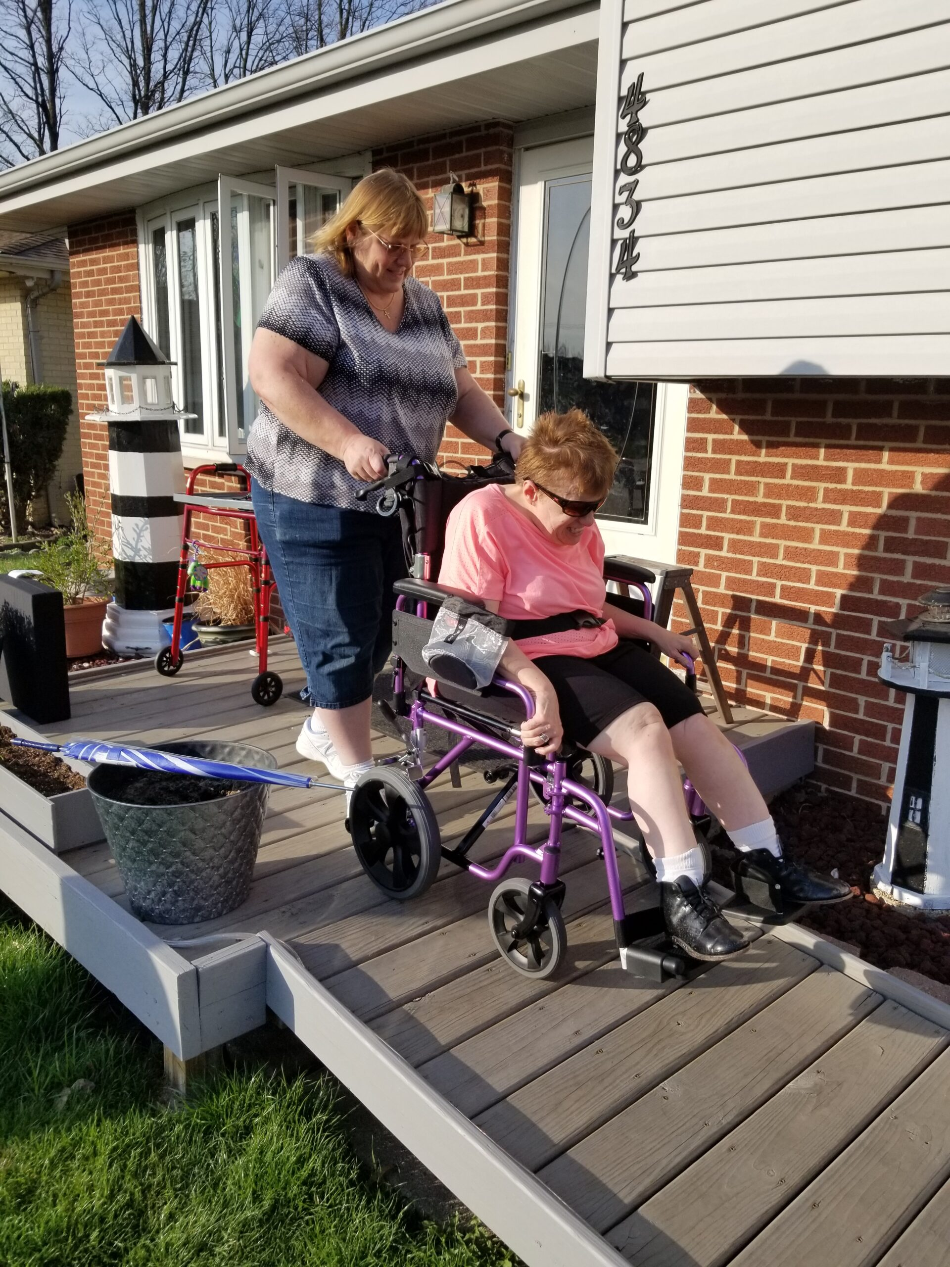 A woman is pushing another woman in a wheelchair on a wooden patio. The wheelchair is purple. The woman in the wheelchair is wearing a pink t shirt and sunglasses. She is smiling and obviously having fun. The woman pushing the chair has medium length hair and is wearing a grey shirt.