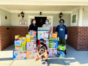 Four people stand around large boxes of household goods