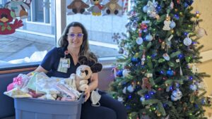 A picture of a female nurse sitting in front of a decorated Christmas tree. She is holding a big box with soft blankets and a stuffed animal- a dog.