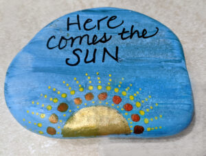 """A painted rock with a blue background, a rising sun, and the text """"Here comes the sun"""""""