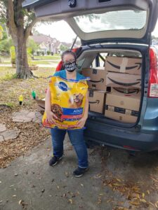 A woman is standing in front of a car holding huge bag of dog food. The car's trunk behind her is open and shows many big cardboard boxes.